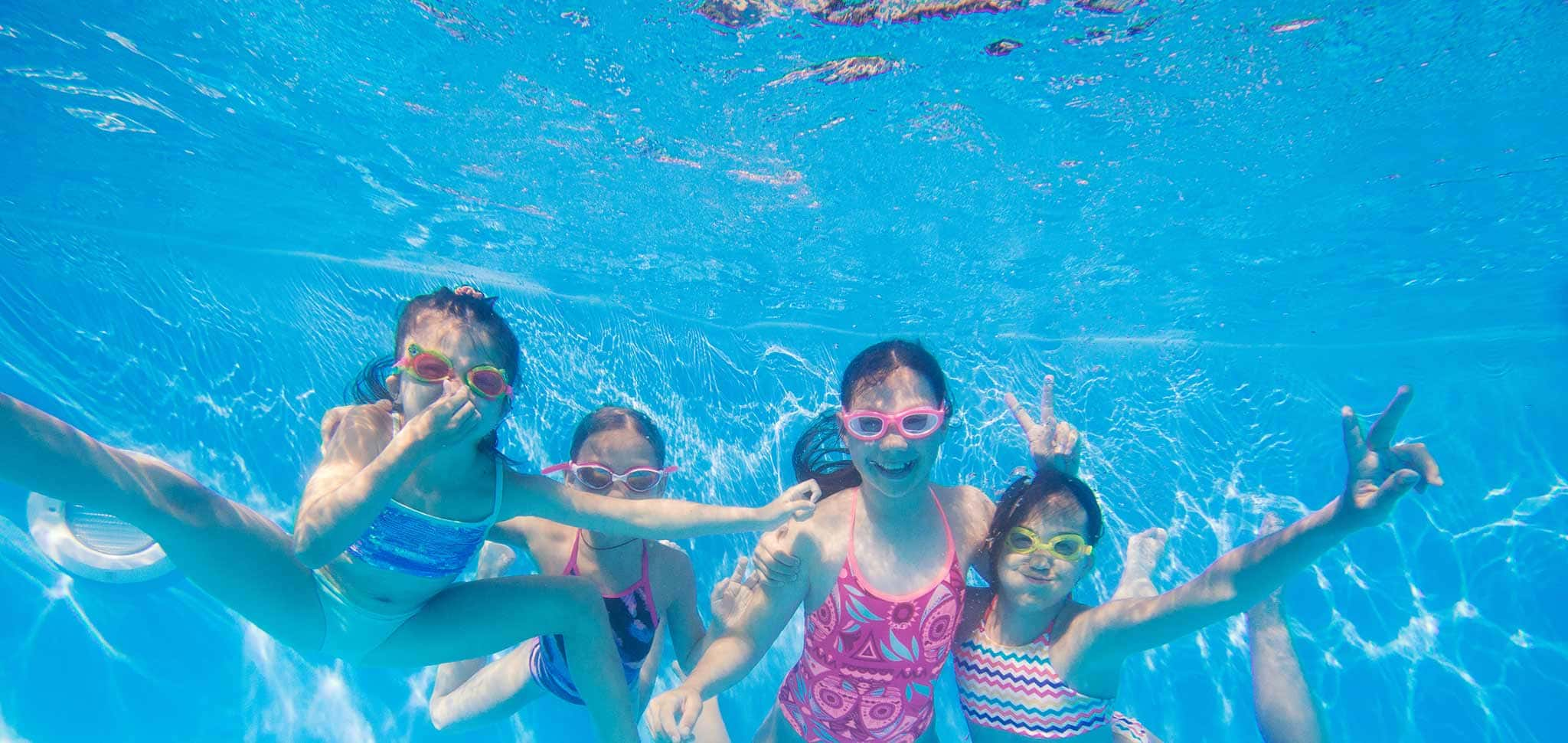 A group of children playing underwater in a swimming pool
